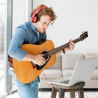 Homem tocando guitarra e olhando para laptop