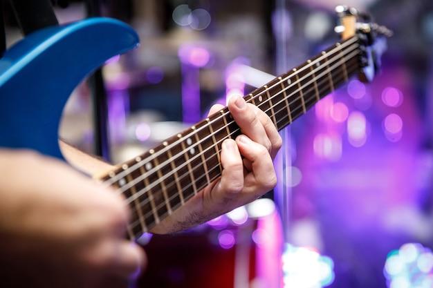 Homem tocando guitarra elétrica, dedos nos trastes