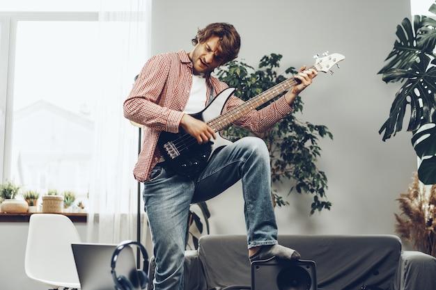 Homem tocando guitarra elétrica e gravando música no laptop em casa