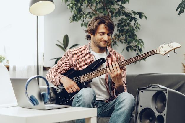 Homem tocando guitarra elétrica e gravando música no laptop