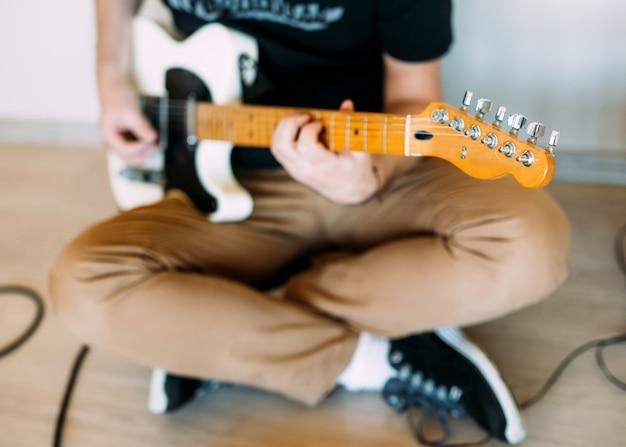 Homem tocando guitarra elétrica em casa, close-up