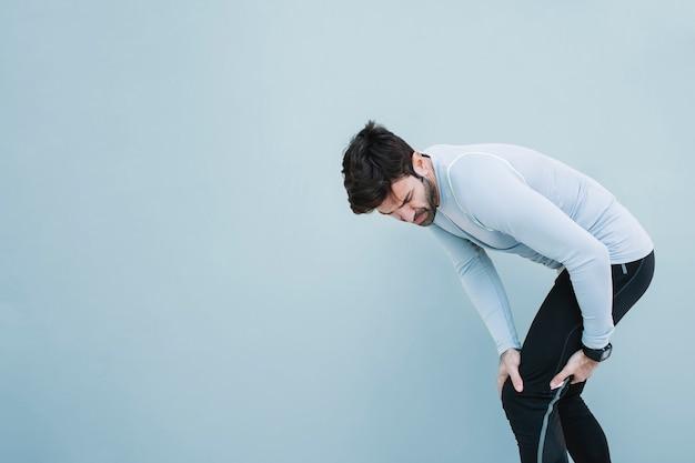 Homem tocando joelho machucado