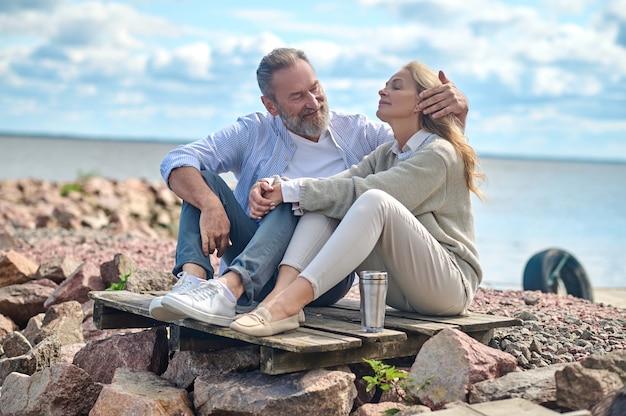 Homem tocando o cabelo de uma mulher sentada perto do mar