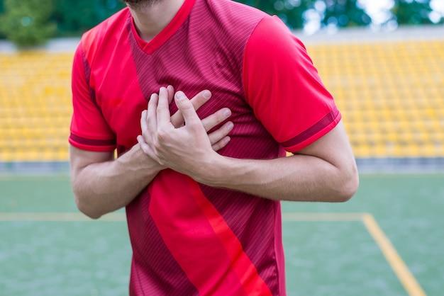 Homem tocando o lado esquerdo do corpo no fundo do estádio