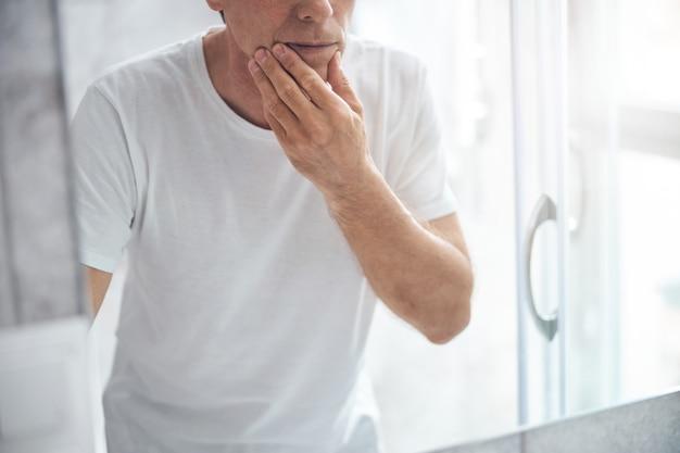 Homem tocando o queixo com a mão na frente do espelho