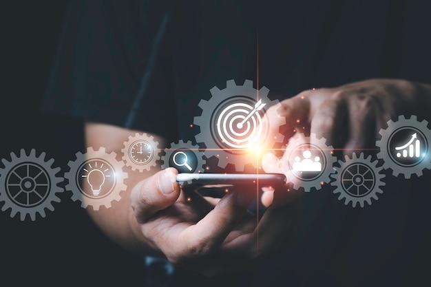 Homem tocando o telefone móvel com engrenagem mecânica virtual e ícone de alvo, conceito de alvo de realização de negócios.