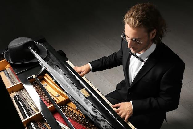 Homem tocando piano de cauda no concerto