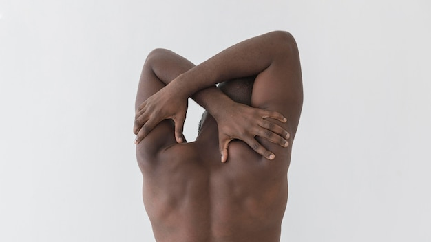 Homem tocando suas costas por trás do tiro
