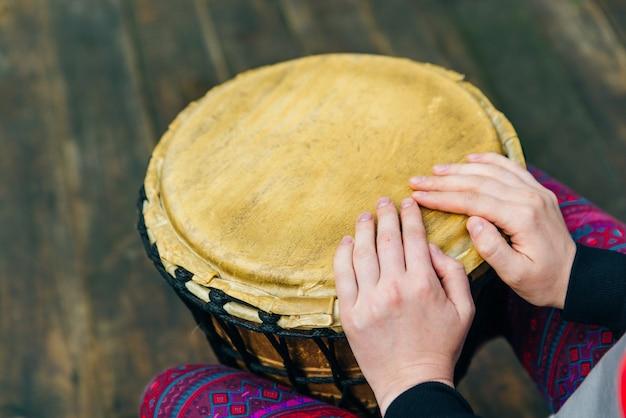 Homem tocando tambor africano djembe, madeira ao ar livre