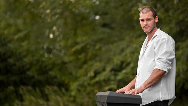 Homem tocando teclado de sintetizador ao ar livre copie o espaço