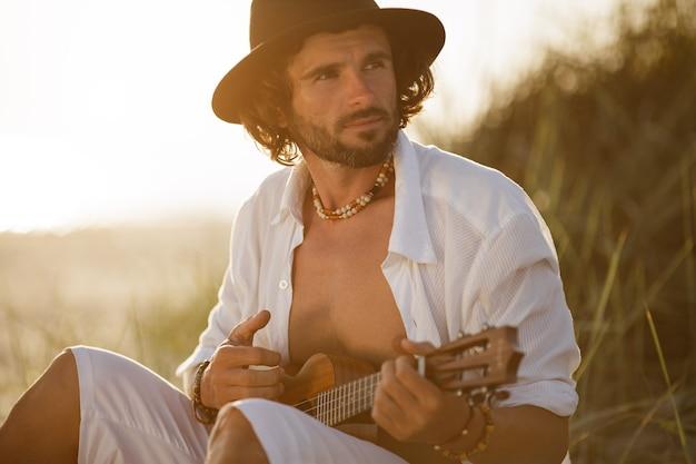 Homem tocando ukulele durante as férias de verão na praia perto do mar