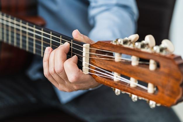 Homem tocando uma nota no violão, praticando uma lição do curso online