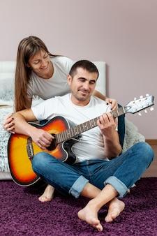 Homem tocando violão, assistido por sua namorada