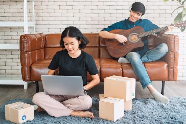 Homem tocando violão com mulher usando laptop no sofá da sala