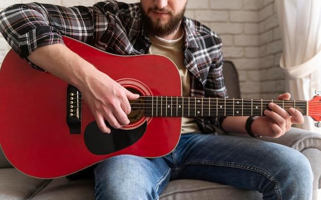 Homem tocando violão de perto