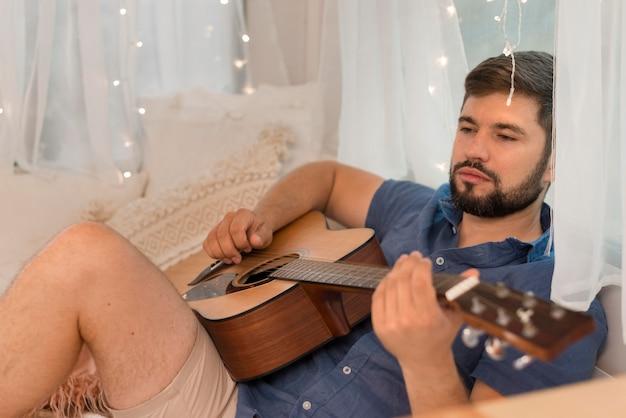 Homem tocando violão dentro de uma caravana