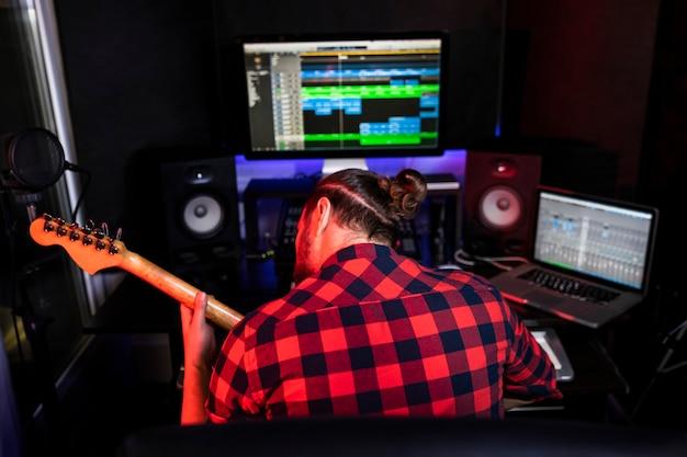 Homem tocando violão e cantando sua nova música em estúdio estéreo para gravar uma faixa totalmente nova