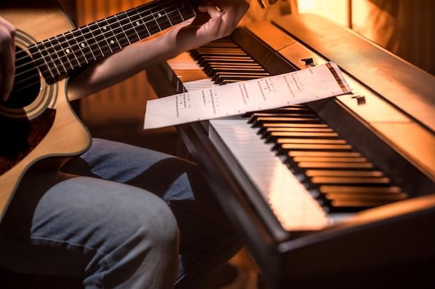 Homem tocando violão e close-up de piano