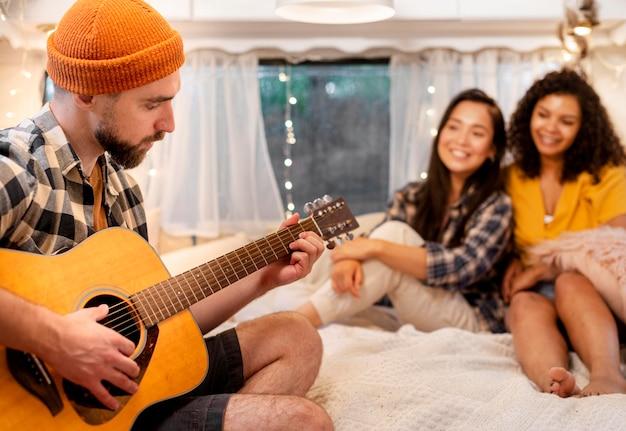 Homem tocando violão e mulheres ouvindo