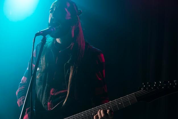 Homem tocando violão e segurando um microfone