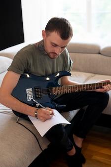 Homem tocando violão em casa