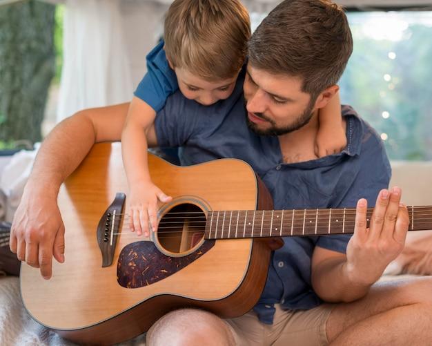 Homem tocando violão em um trailer ao lado de seu filho