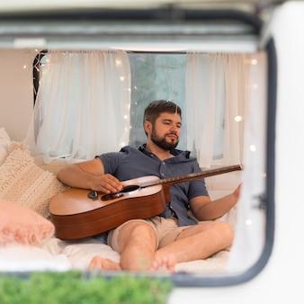 Homem tocando violão em uma caravana