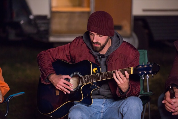 Homem tocando violão em uma noite fria de outono em um acampamento para seus amigos com uma van de campista retrô ao fundo.