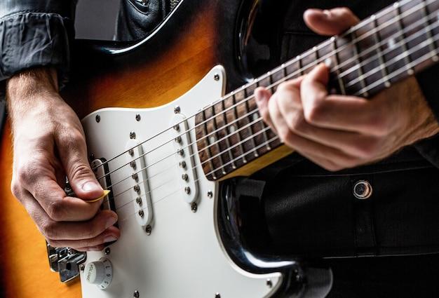 Homem tocando violão. feche a mão tocando violão. músico tocando violão