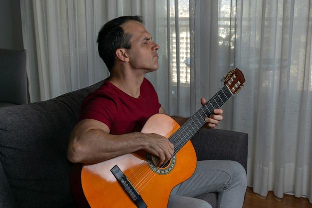 Homem tocando violão na sala de estar e fazendo um solo.