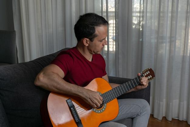 Homem tocando violão na sala de estar e olhando para baixo.