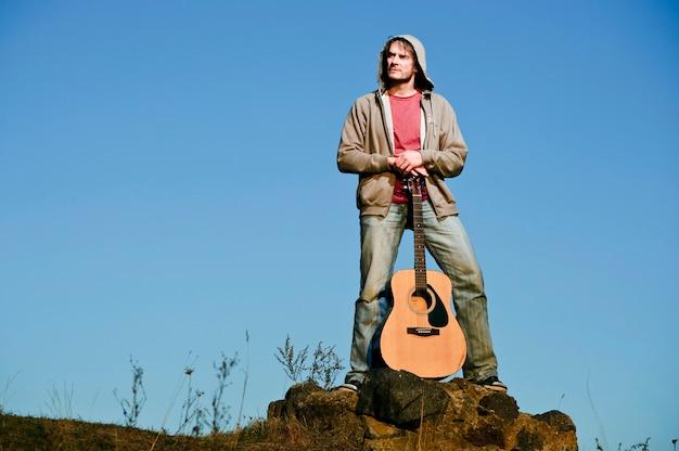 Homem tocando violão no campo por do sol.