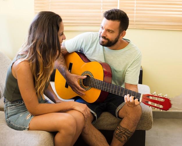 Homem tocando violão para sua linda esposa em casa