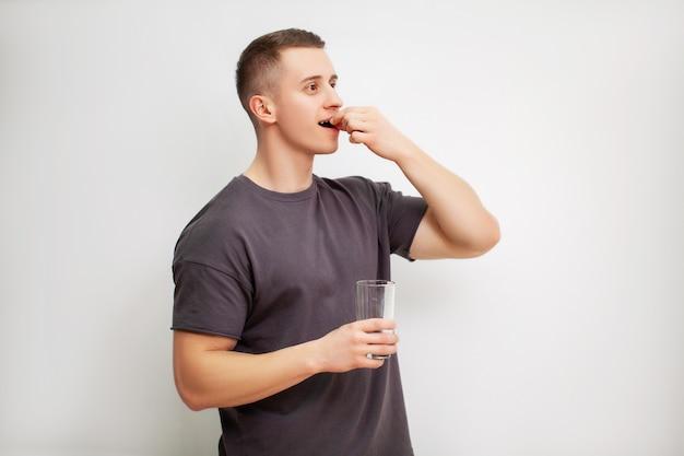 Homem toma um comprimido de aminoácidos após o treino.