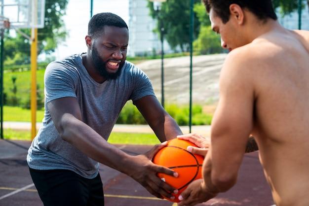 Homem tomando bola do outro homem