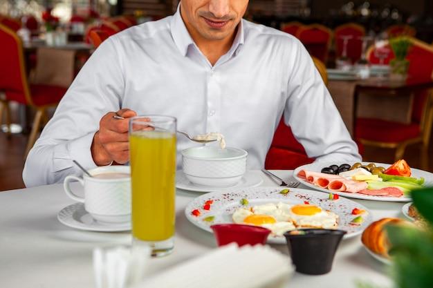 Homem tomando café da manhã comendo aveia no quarto