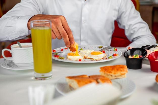 Homem tomando café da manhã comendo ovos fritos, vista lateral.