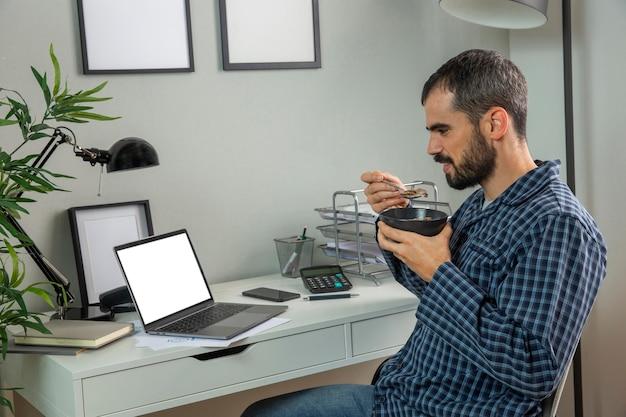 Homem tomando café da manhã enquanto trabalha em casa