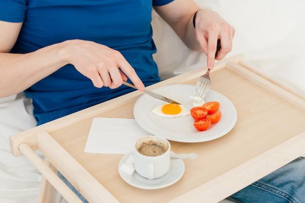 Homem tomando café da manhã na cama