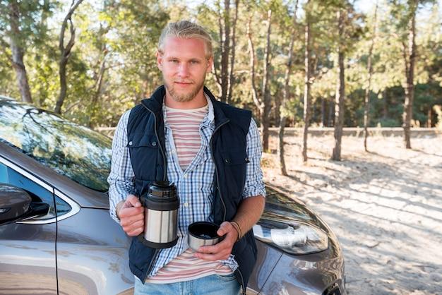 Homem tomando café e sentado ao lado do carro