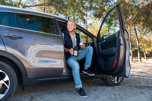 Homem tomando café e sentado na frente do carro