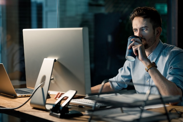Homem tomando café e trabalhando até tarde
