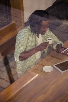 Homem tomando café e usando smartphone