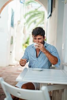 Homem tomando café em um café de rua