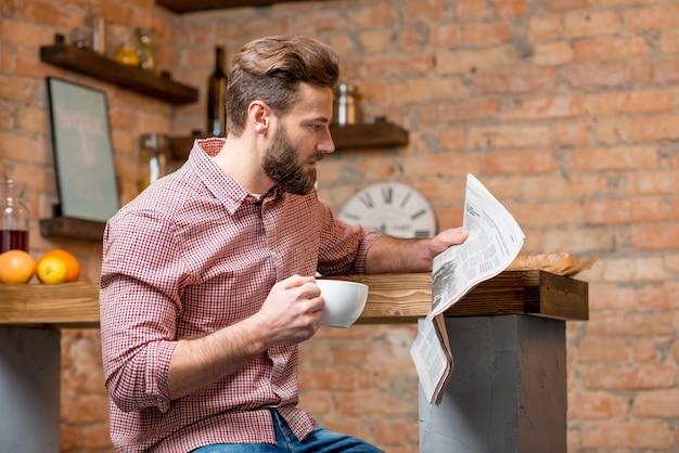 Homem tomando café na cozinha