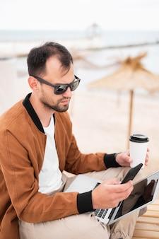 Homem tomando café na praia e trabalhando no laptop