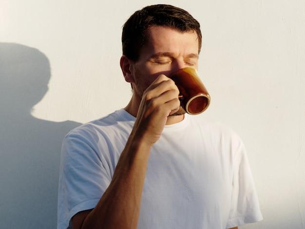 Homem tomando café na varanda manhã de verão.