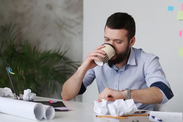 Homem tomando café no escritório