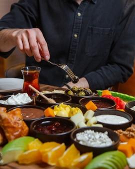 Homem tomando comida da mesa de café da manhã totalmente doada com alimentos misturados.