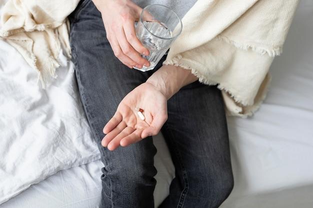 Homem tomando seus comprimidos na cama